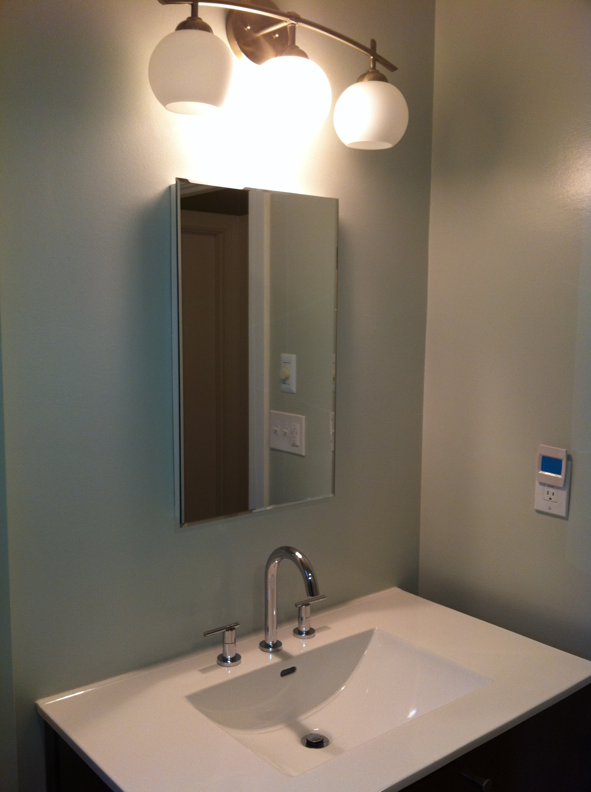 On the opposite corner of the bathroom is an inset medicine cabinet and a  one-piece countertop with integral sink. Notice that the mirror is  perfectly ...