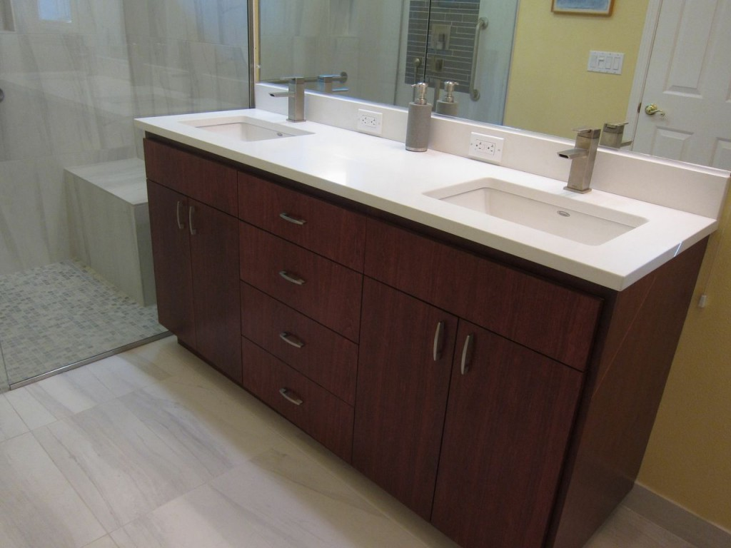 This solid surface countertop enhances the rich wood vanity.